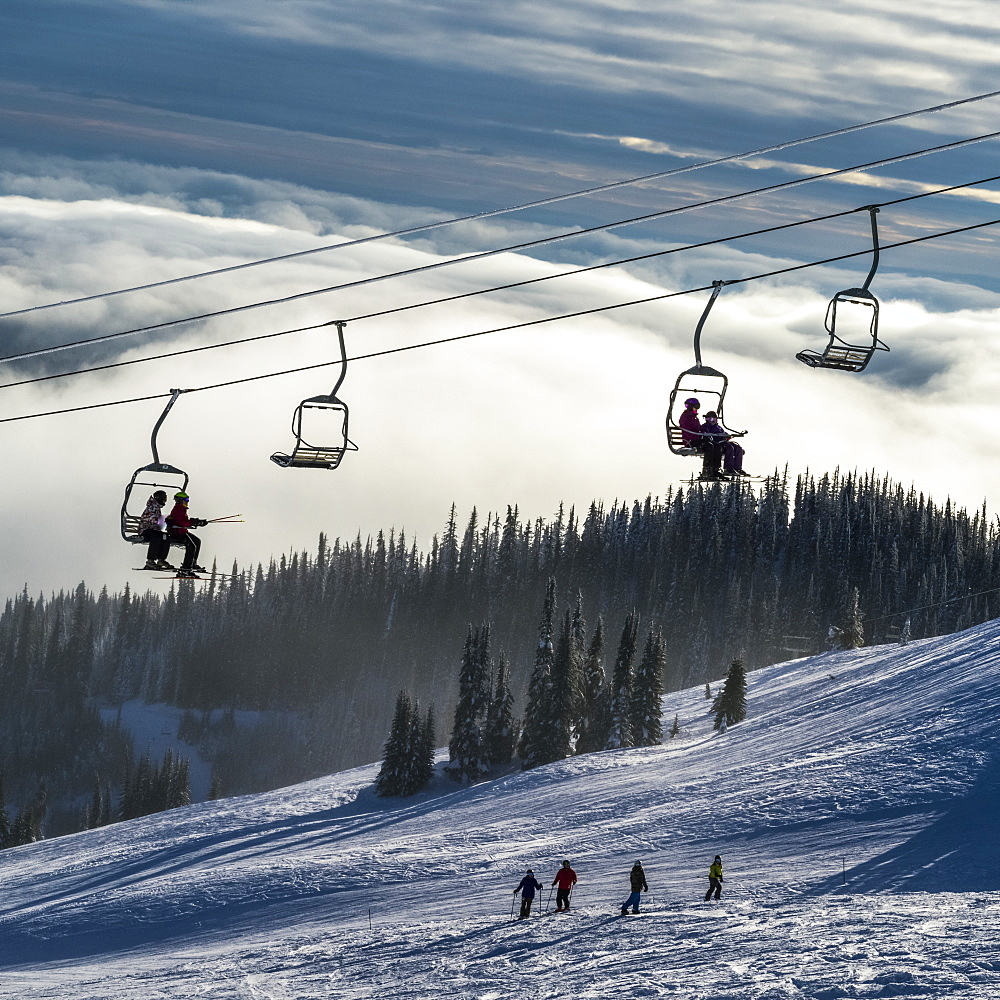 Skiers on a chairlift and on the slope below at Sun Peaks ski resort, Kamloops, British Columbia, Canada