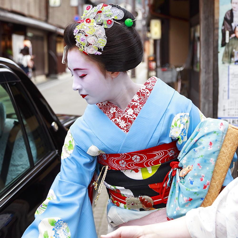 Maiko, apprentice geisha, leaves okiya (geisha house) to get in a car on way to evening appointment, Gion, Kyoto, Japan, Asia