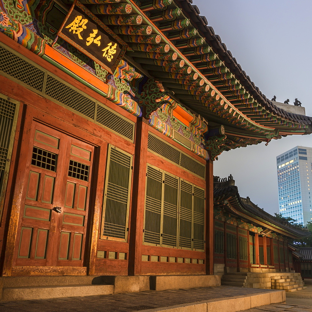 Deoksugung Palace, traditional Korean building, illuminated at dusk, with modern building in distance, Seoul, South Korea, Asia