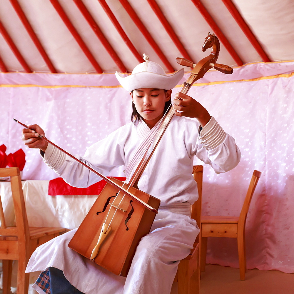 Young man in traditional dress plays horse head fiddle in a ger, Gobi Desert, Mongolia, Central Asia