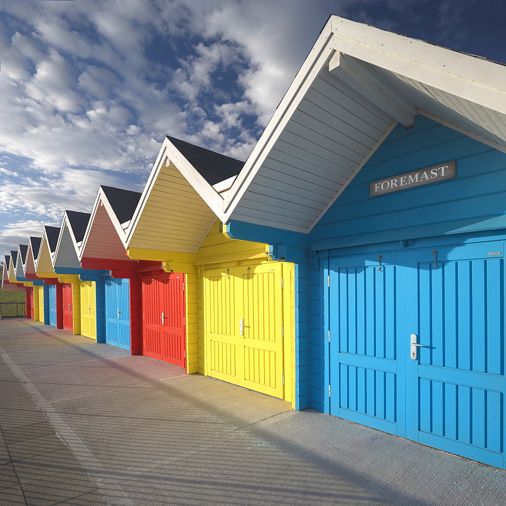 Row of colourful beach huts lit by early morning summer sunlight on the seafront at Whitby, North Yorkshire, England, United Kingdom, Europe - 1266-15