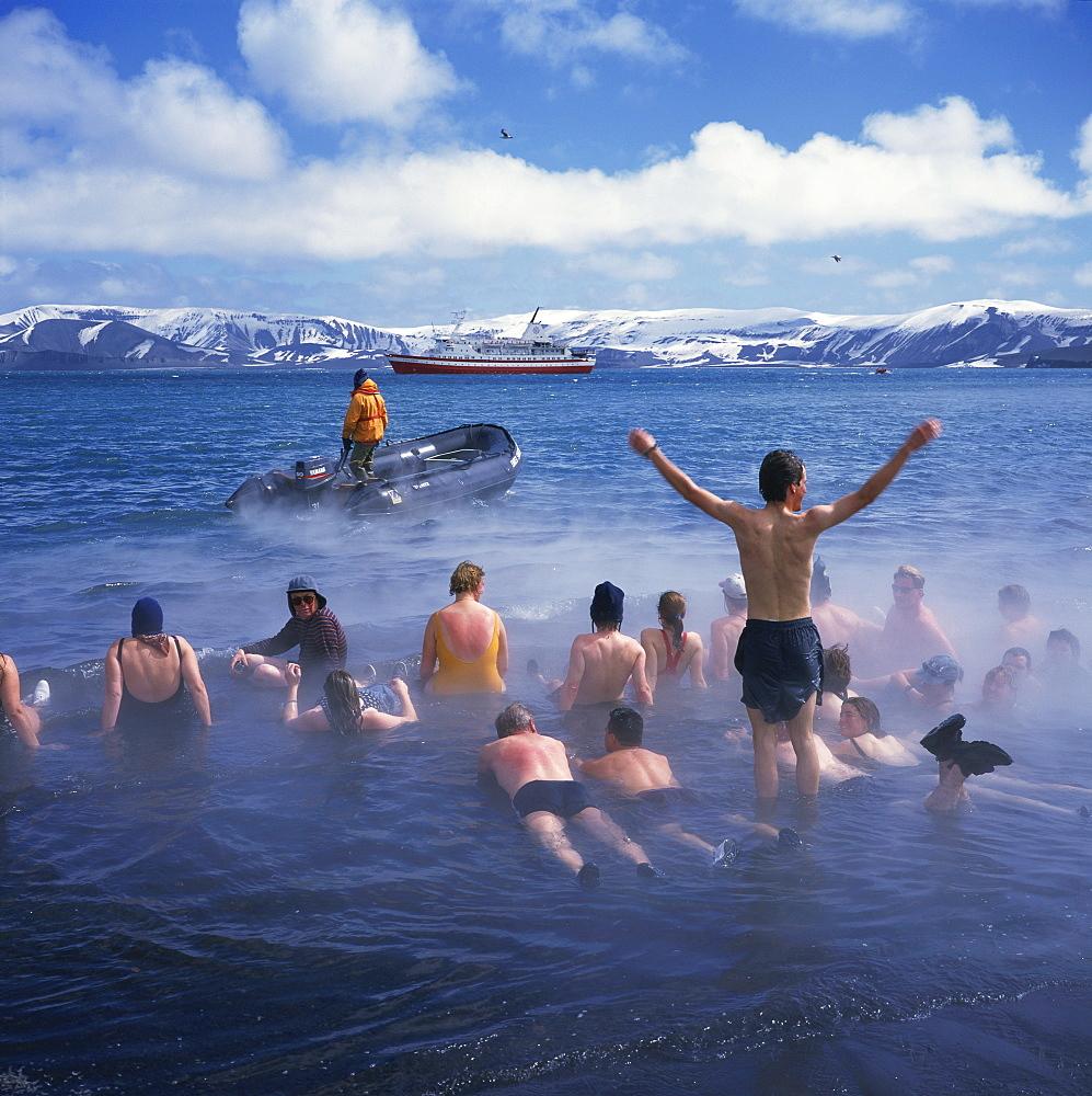 Tourists bathe in hot tub in warm waters of dormant volcano on Deception Island, Antarctica, Polar Regions