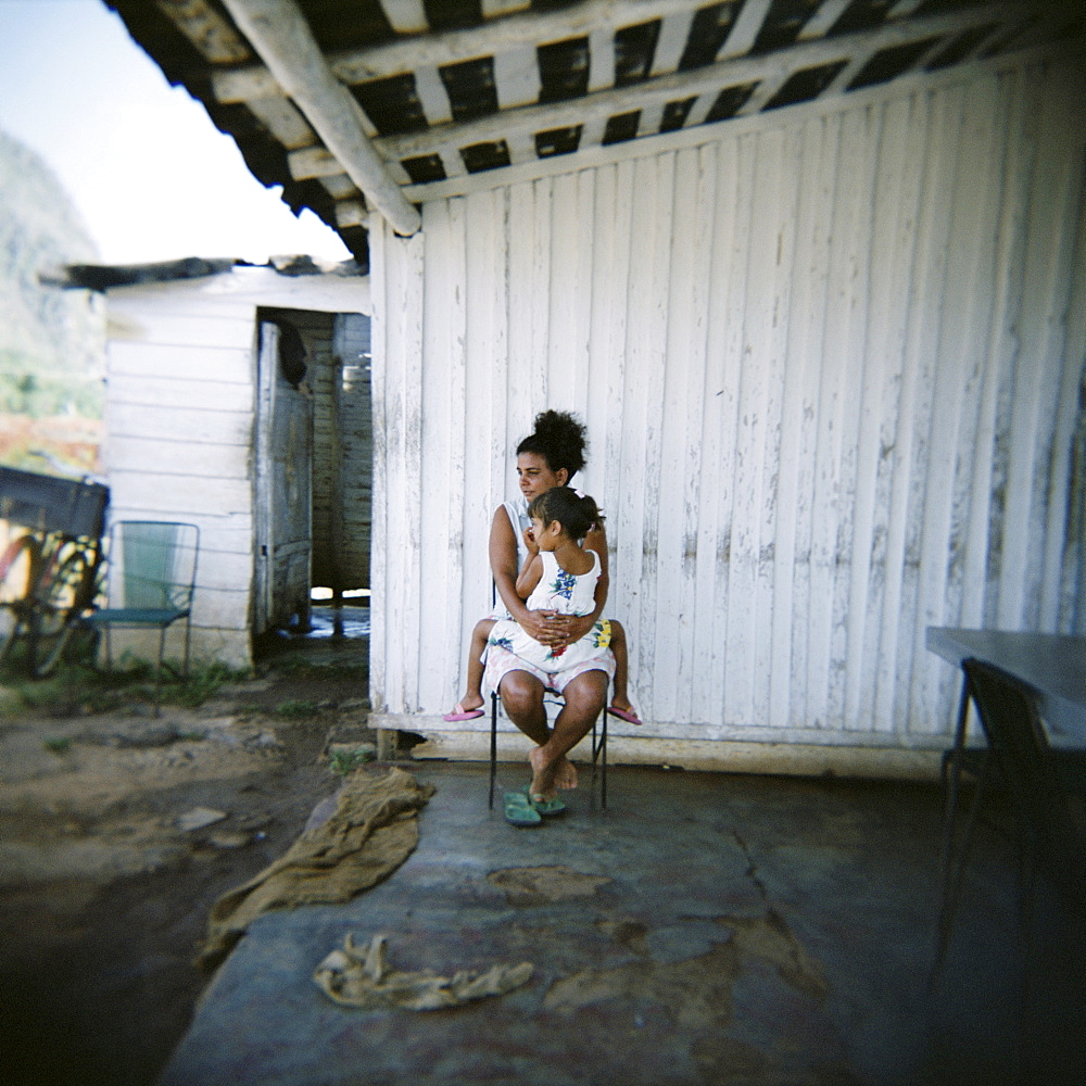 Mother and daughter on porch of their farm, Vinales, Cuba, West Indies, Central America