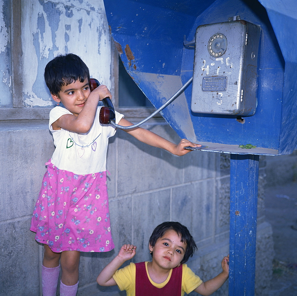 Two small Uzbek girls using the public telephone in Bukhara, Uzbekistan, Central Asia, Asia