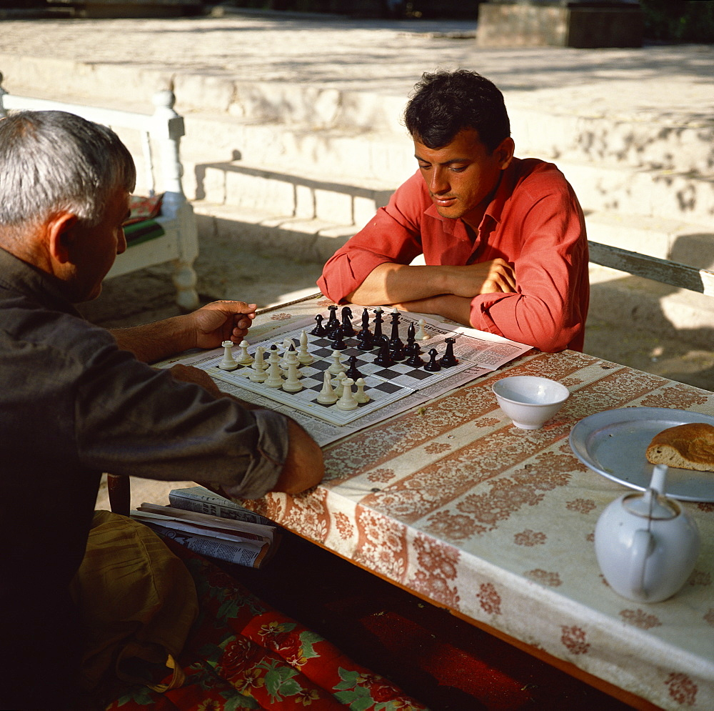 Uzbek men playing chess in a tea house garden, Bukhara, Uzbekistan, Central Asia, Asia