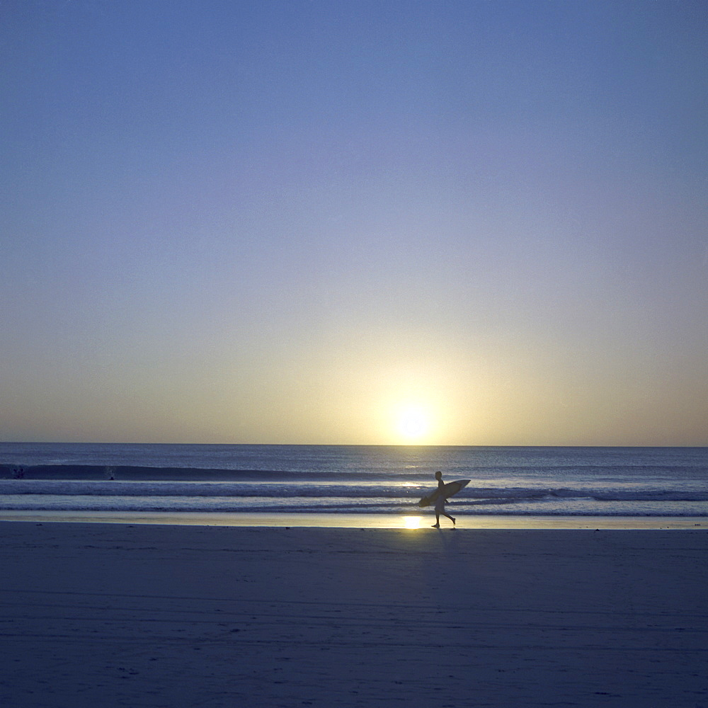 Silhouette of surfer walking on Avellanas Beach, Nicoya Peninsula, Costa Rica, Central America