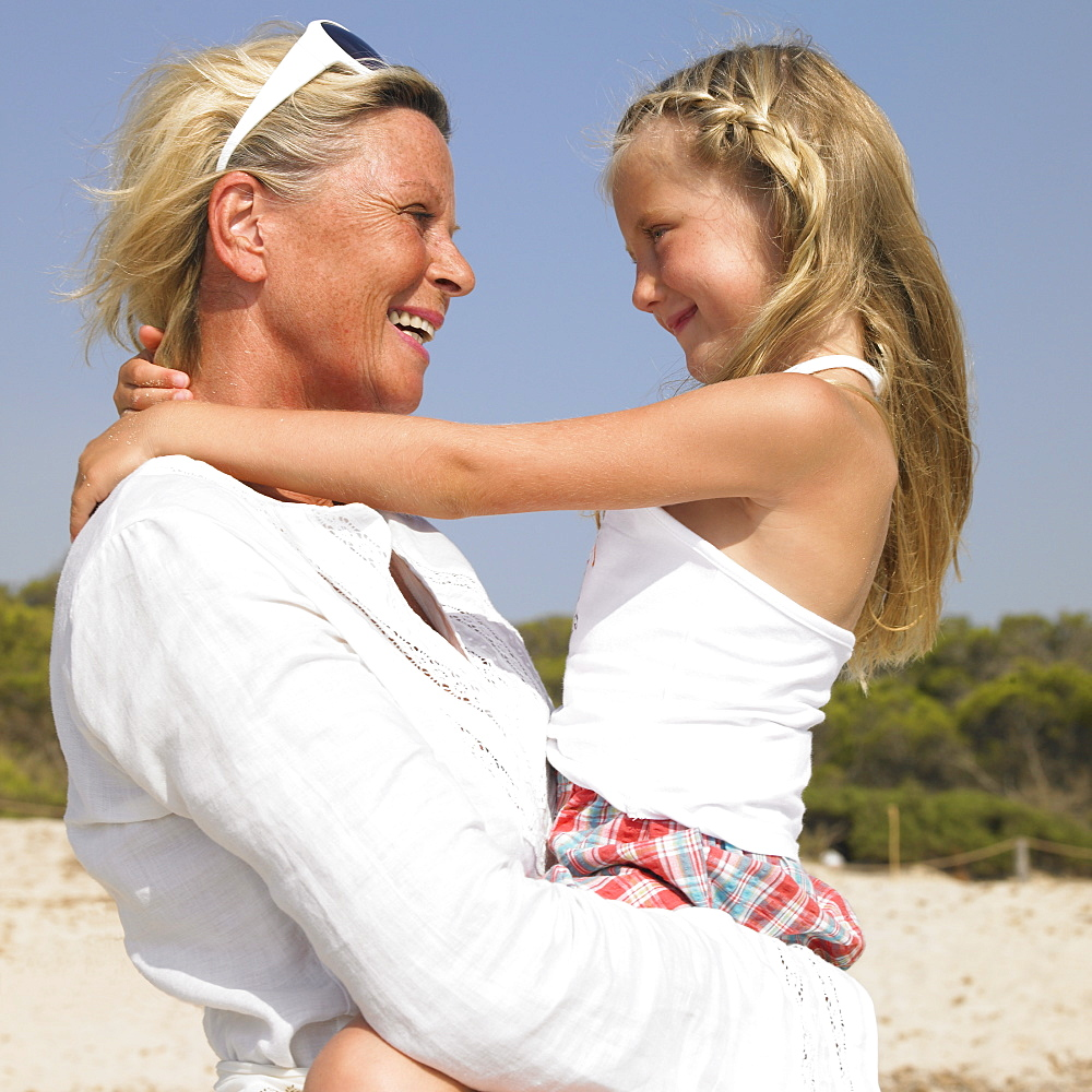 Grandmother and grandaughter (6-8) on beach