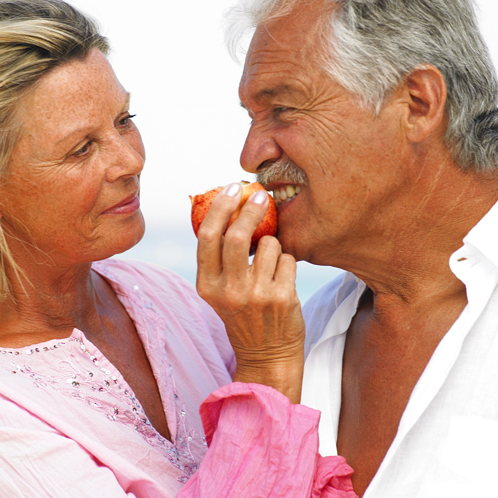 senior couple on beach holding apple - 768-168