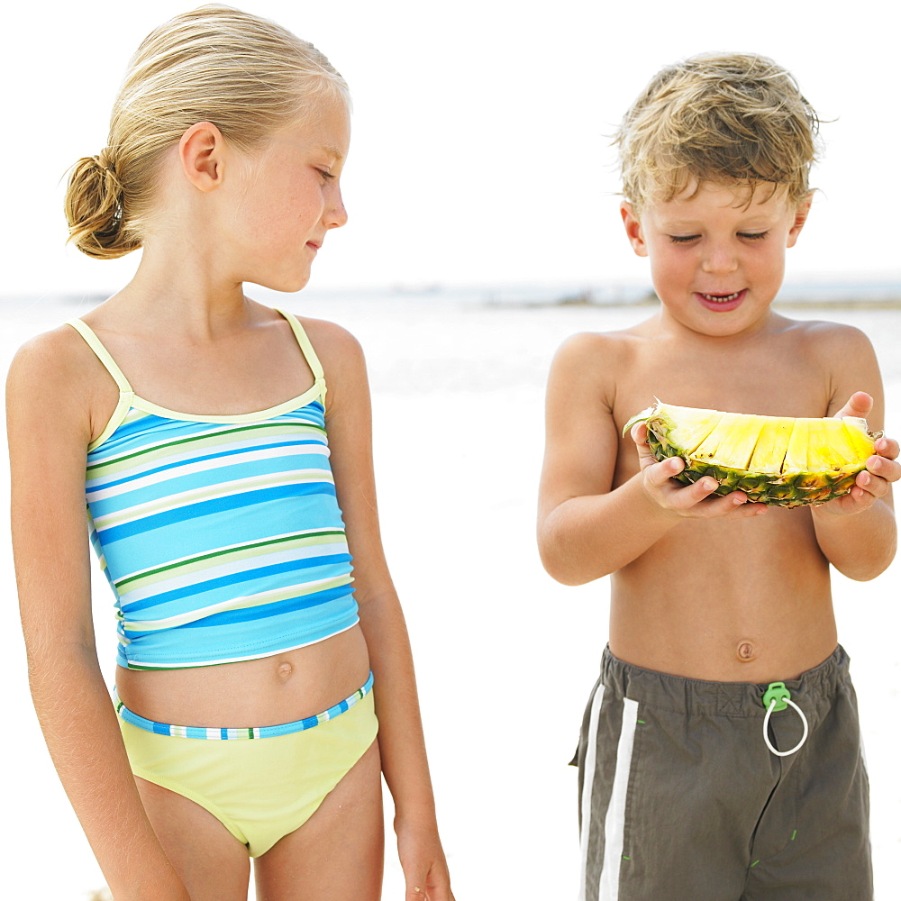 Boy and girl (6-8) on beach, boy holding - 768-267