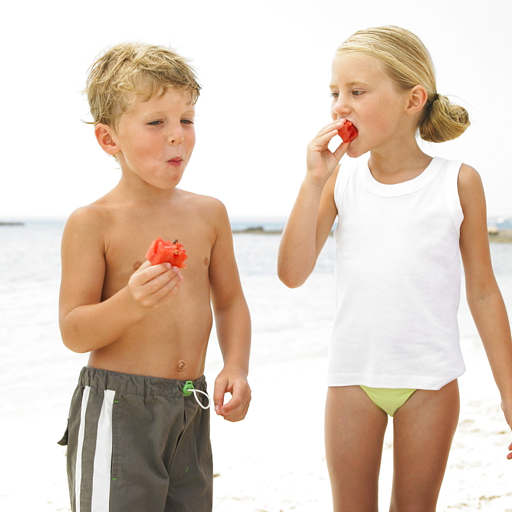 Boy and girl (6-8) on beach eating watermelon - 768-268