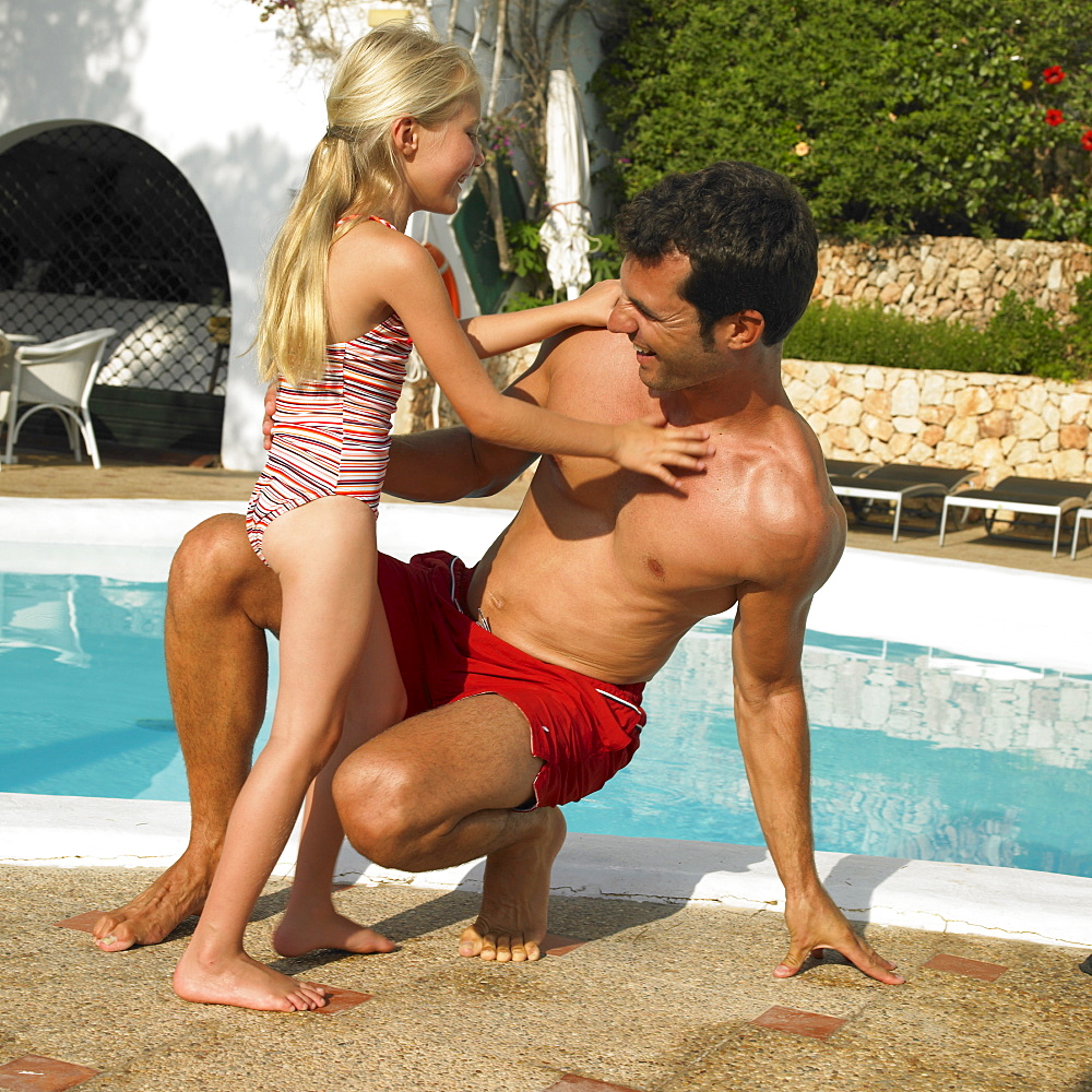 Father and daughter (6-8) playing together by swimming pool