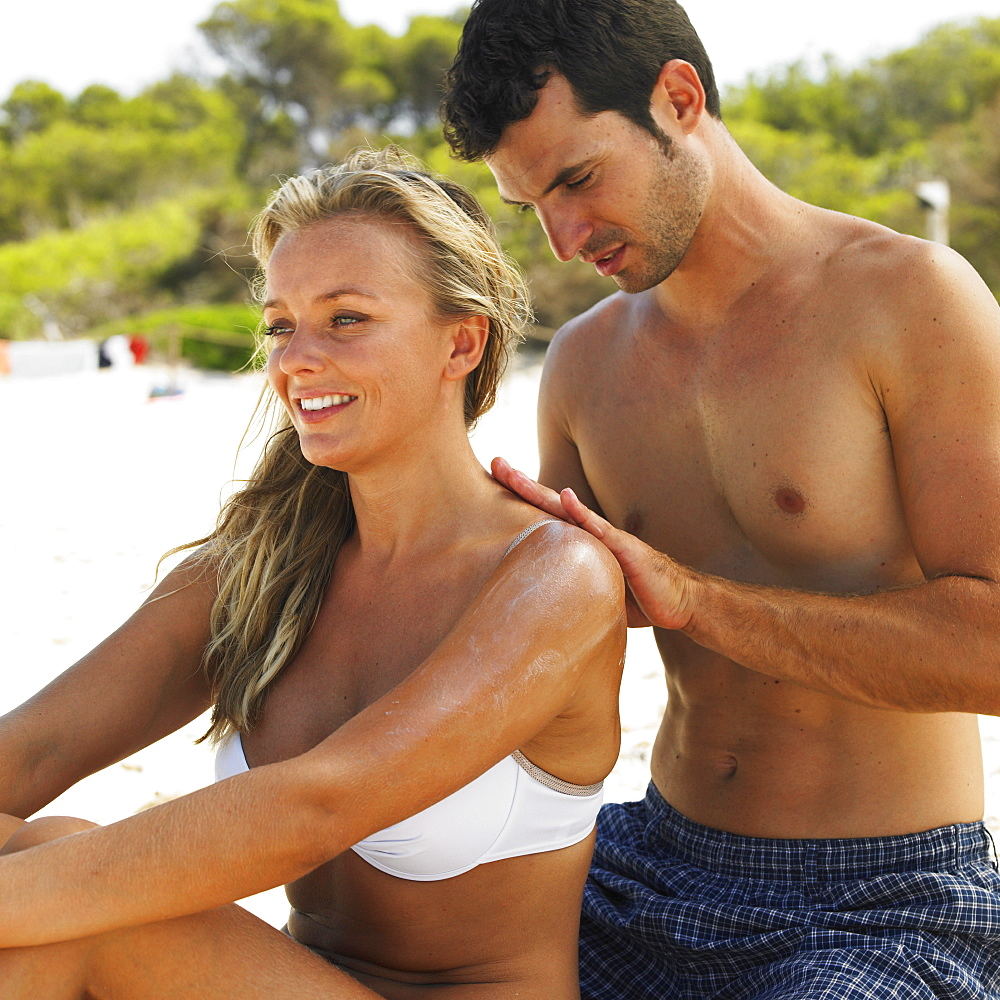 Man applying suncream to woman's back on beach