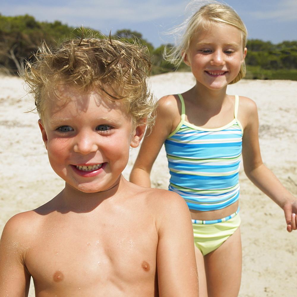 Boy and girl (6-8) on beach
