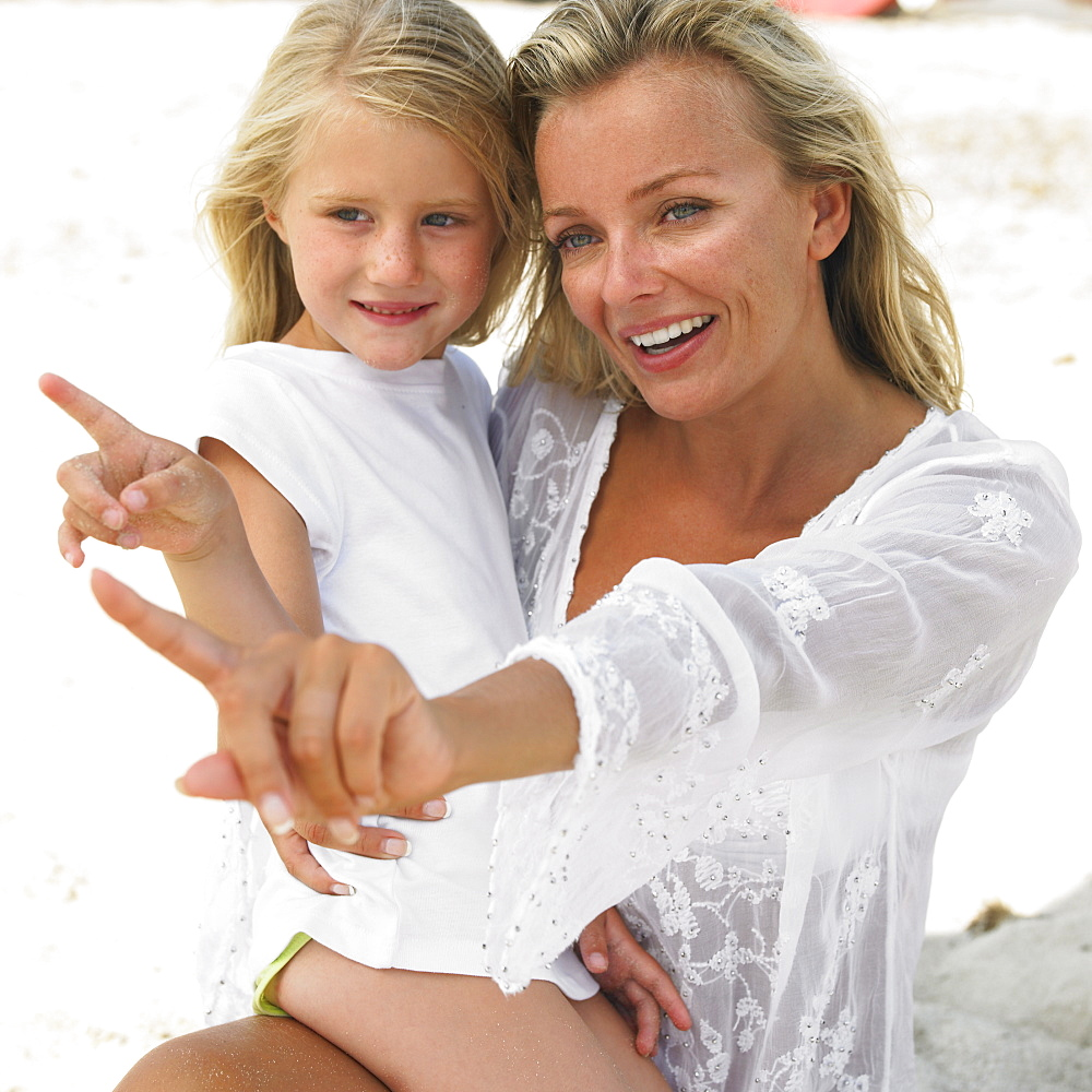Mother and daughter (6-8) on beach