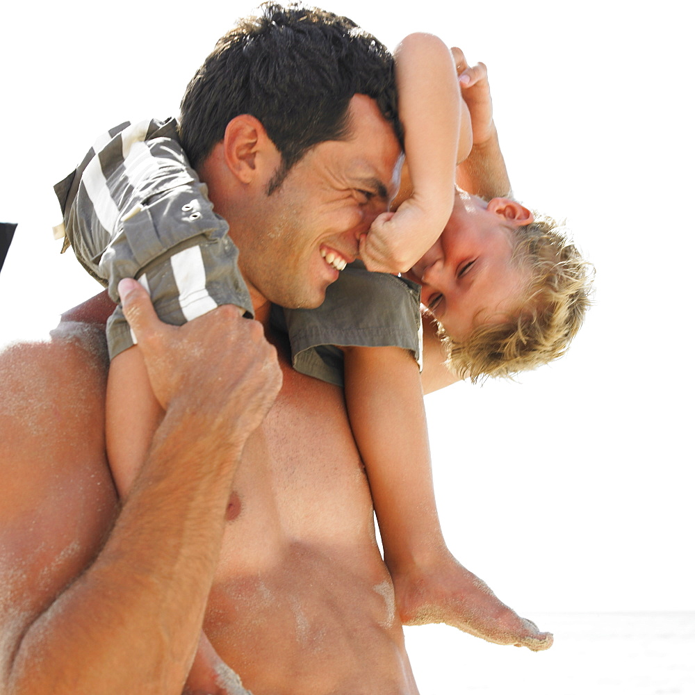 Son (6-8) sitting on father's shoulders on beach