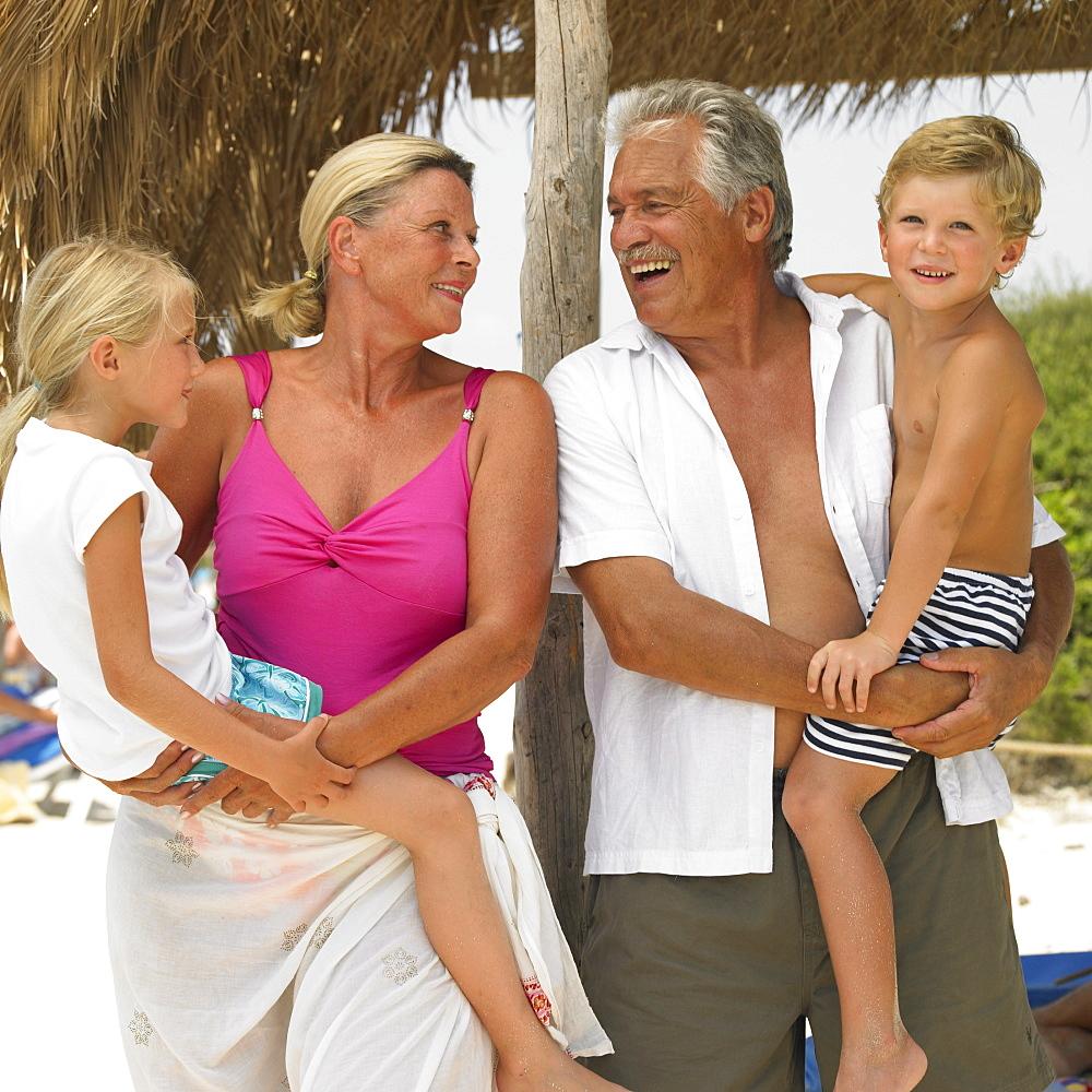 Grandparents and grandchildren (6-8) on the beach under parasol