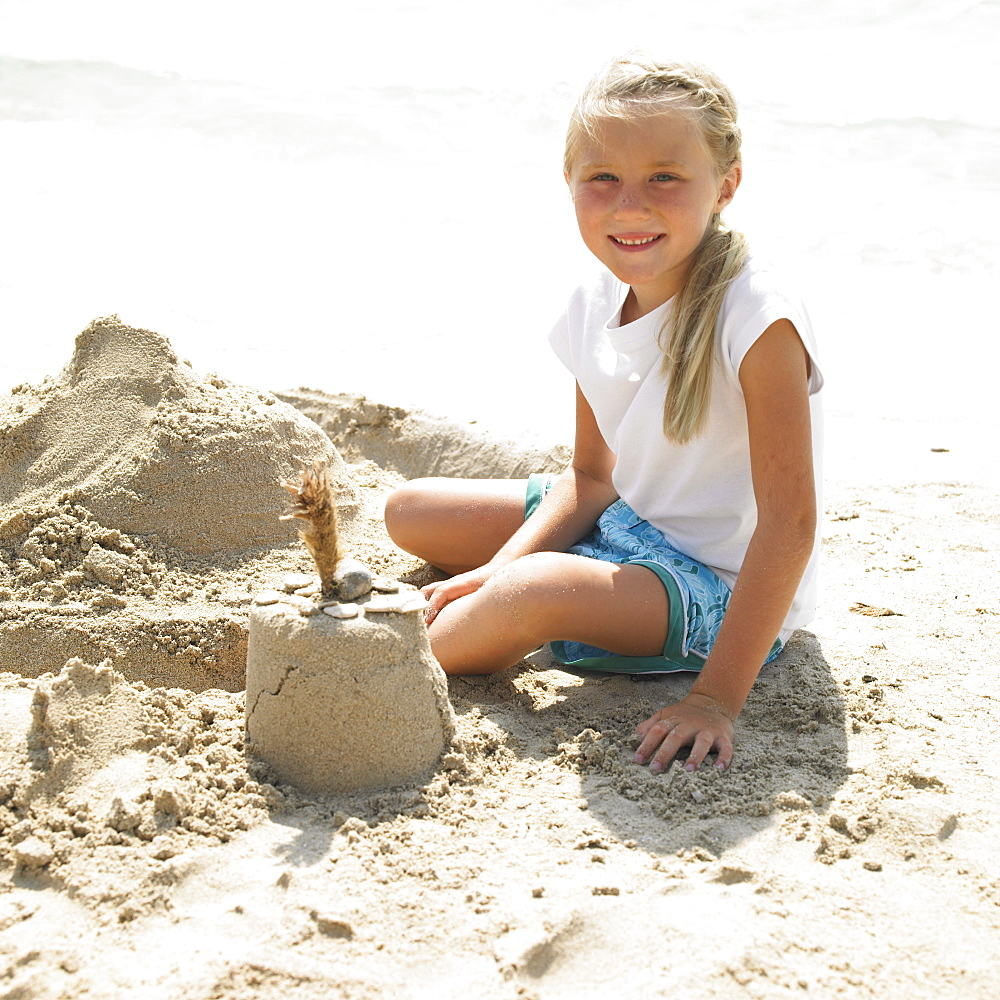 Girl (6-8) making a sandcastle on the beach