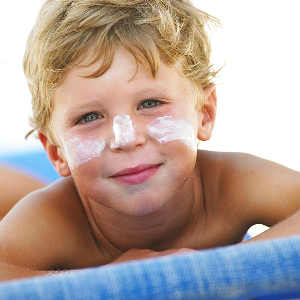 Boy (6-8) on beach with suncream on face