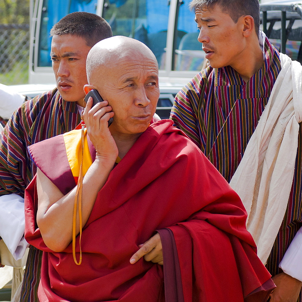 Bhutan, , Red robed Tibetan Buddhist monk talking on his mobile phone.