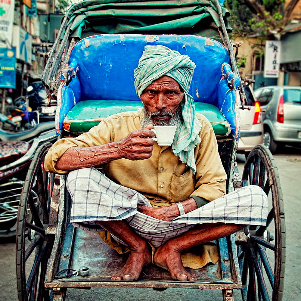 Rickshaw wallah taking a cup of indian tea on his rickshaw  Calcutta, India