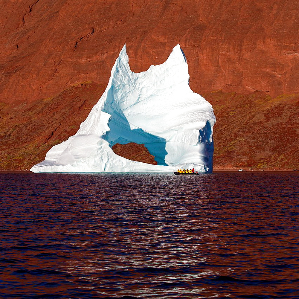 Tourist in a Zodiac exploring icebergs, Scoresbysund, Greenland.