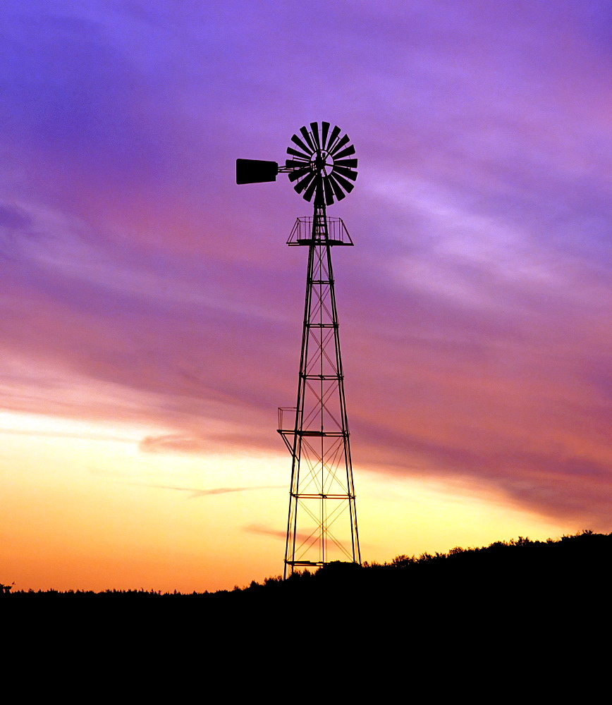 Wind pump silhouetted against colourful night sky