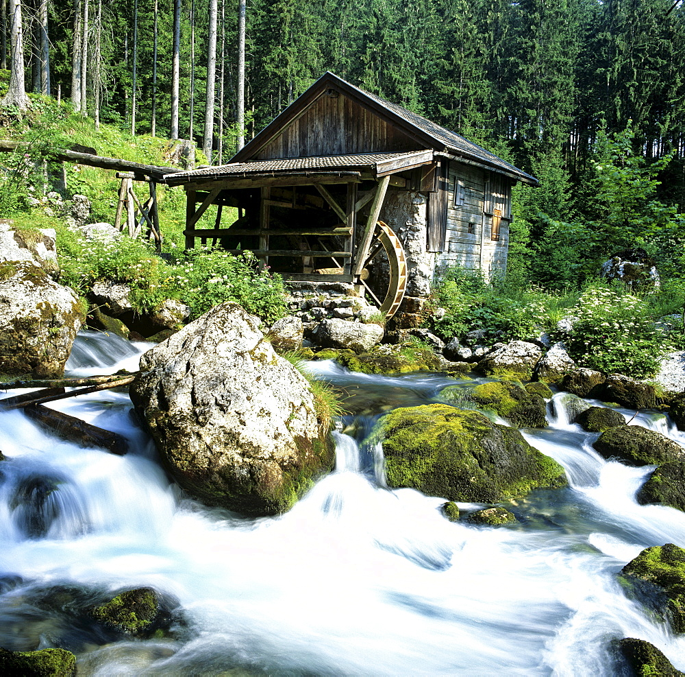 Watermill wheel beside a small waterfall in a mountain stream with moss-covered rocks