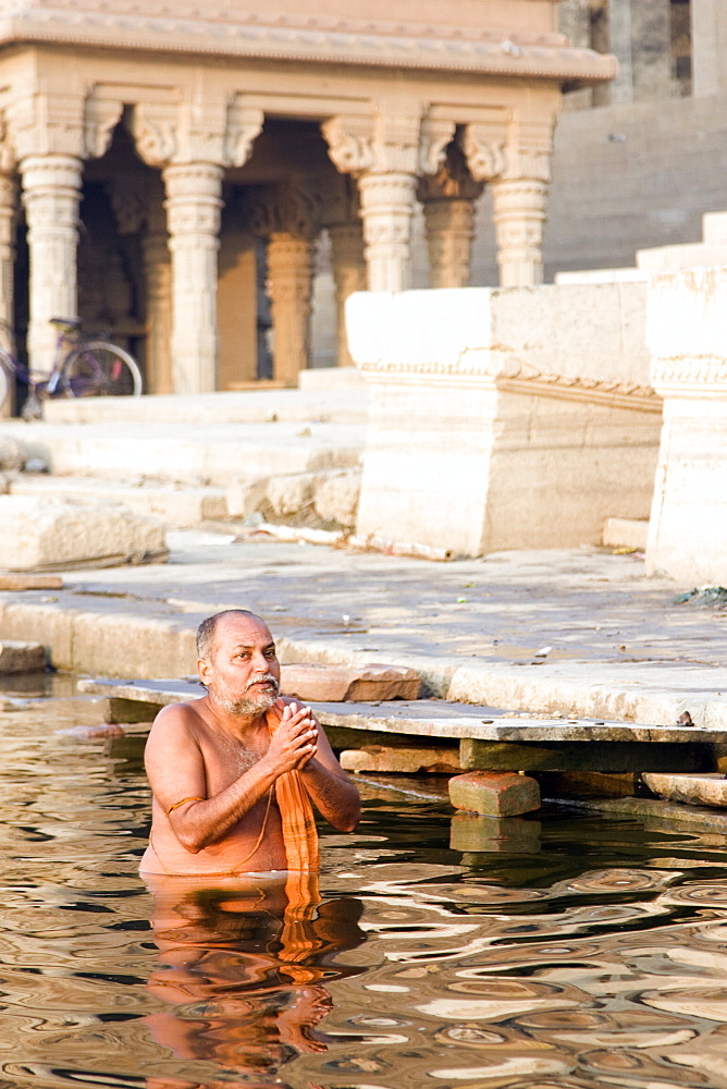Hindu pilgrims and local people wash and worship in the river ganges at a Varanasi ghat, India. - 1005-5