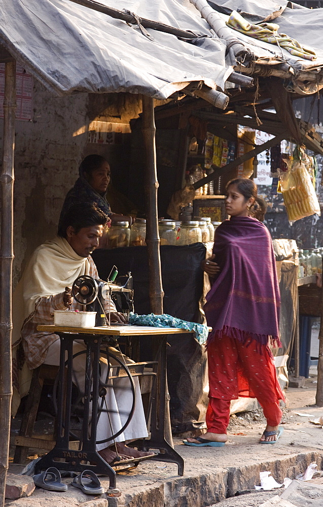A tailor mends an article of clothing while a young girl looks on. Kali Ghat, Calcutta, India.