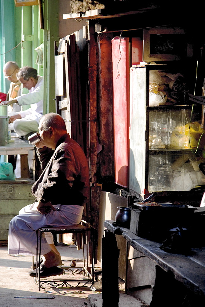 A shopkeeper enjoys a chai while tending his shop on  Tagore Street, Kolkata, India