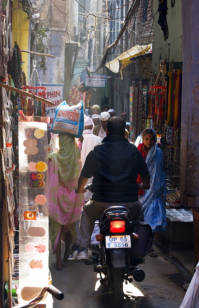 A man attempts to ride his motorbike down a busy street in the oldtown area of Varanasi, India - 1005-87