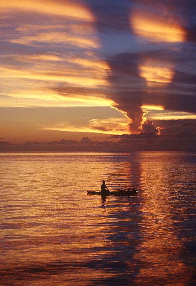 Person in canoe on sunset-orange lagoon .Papua New Guinea