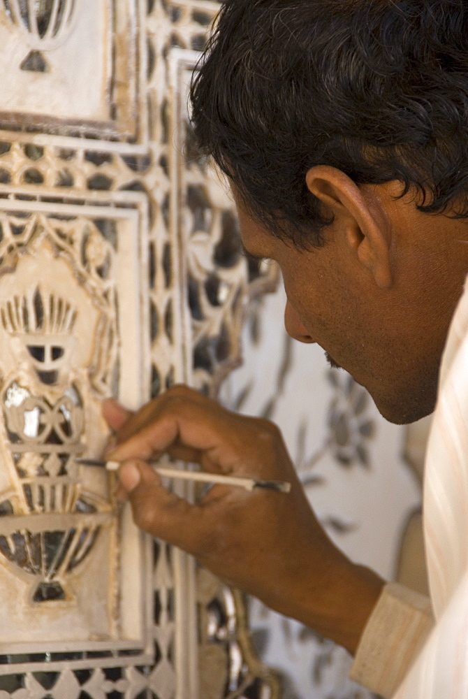 Artisan carrying out repairs on the plasterwork relief at the Amber Fort, Rajasthan, India