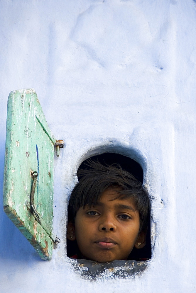 Young boy looking through small window, Udaipur, Rajasthan, India