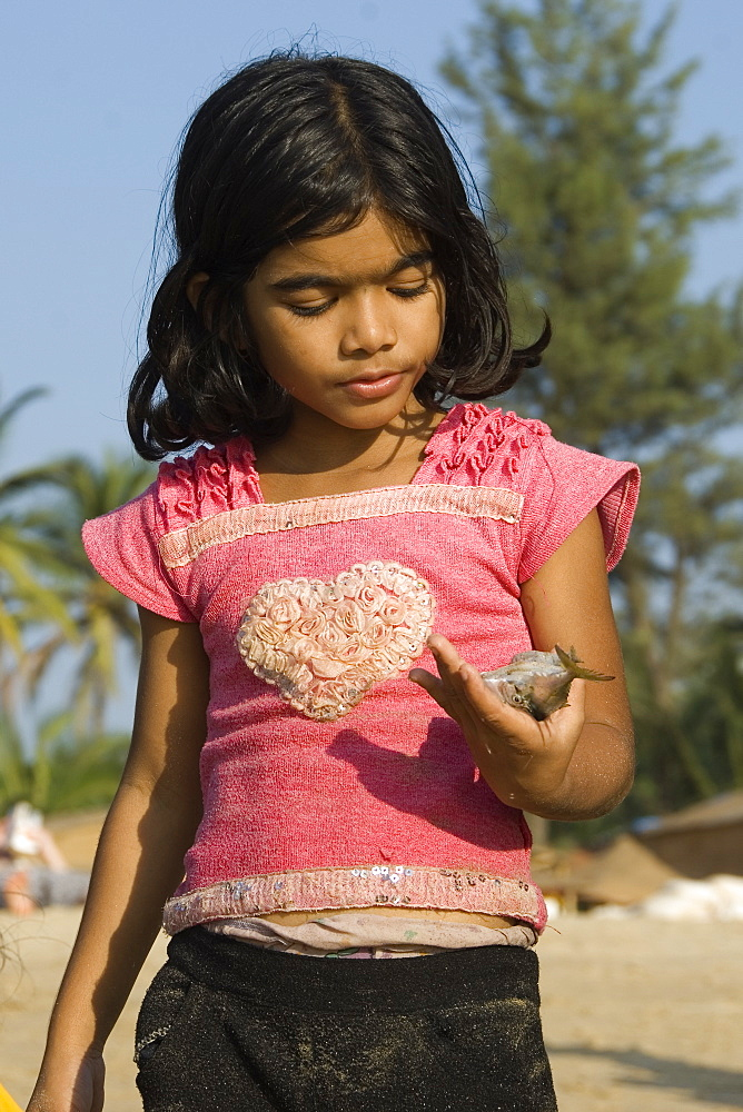Young girl on the beach looking at a fish in her hand, Goa, India - 1024-345