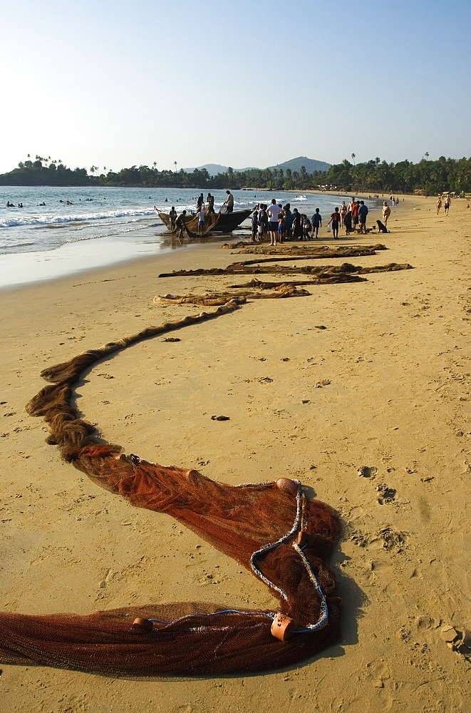 Fishing net laid out on the beach after hauling in the fish, Goa, India