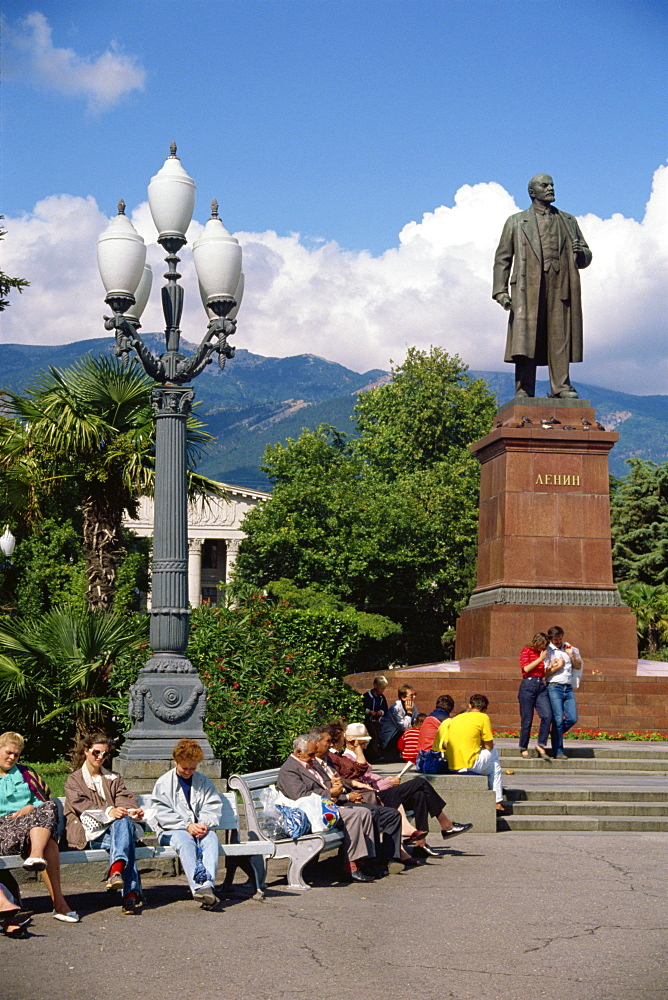 People sitting on benches near a statue of Lenin in Yalta, the Crimea, Ukraine, Europe