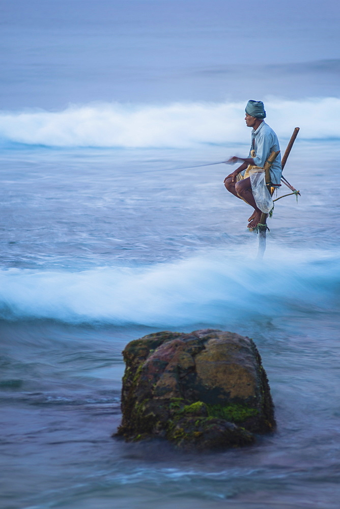 Stilt fishing, a stilt fisherman in the waves at Midigama near Weligama, South Coast, Sri Lanka, Indian Ocean, Asia