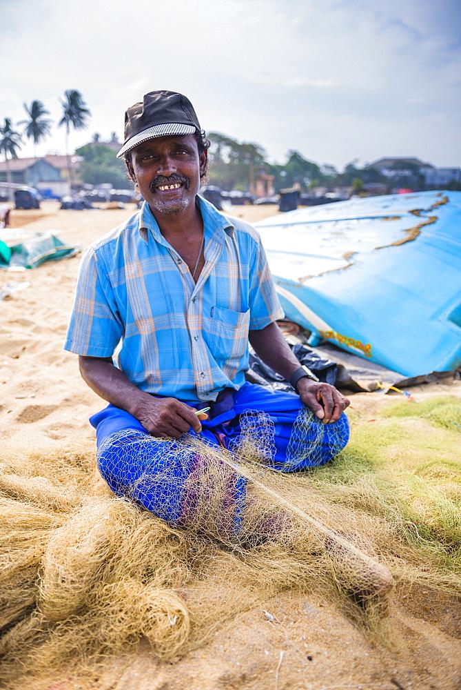 Portrait of a fisherman mending nets in Negombo (Lellama), Sri Lanka, Asia