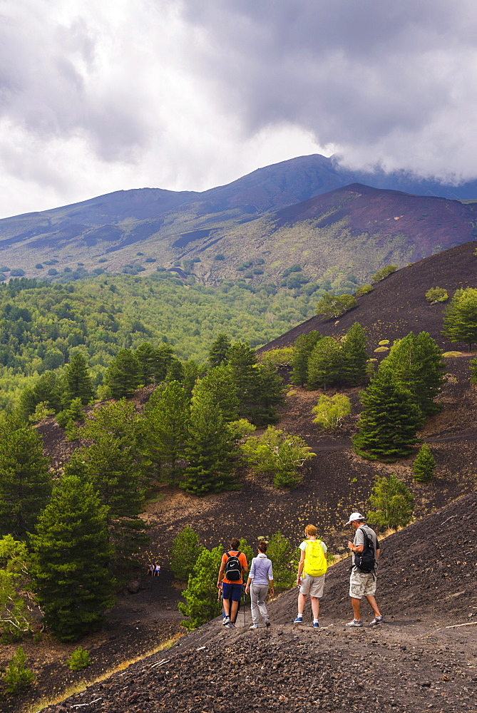 Tourists hiking on an old lava flow from an eruption, Mount Etna, UNESCO World Heritage Site, Sicily, Italy, Europe