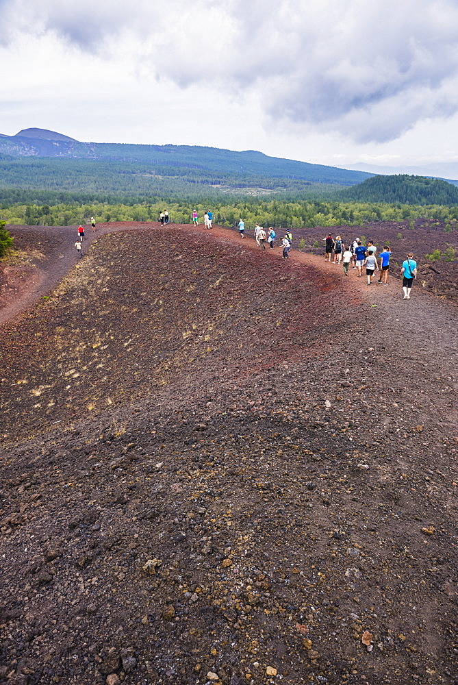 Tourists exploring an old lava flow from an eruption of Mount Etna Volcano, UNESCO World Heritage Site, Sicily, Italy, Europe