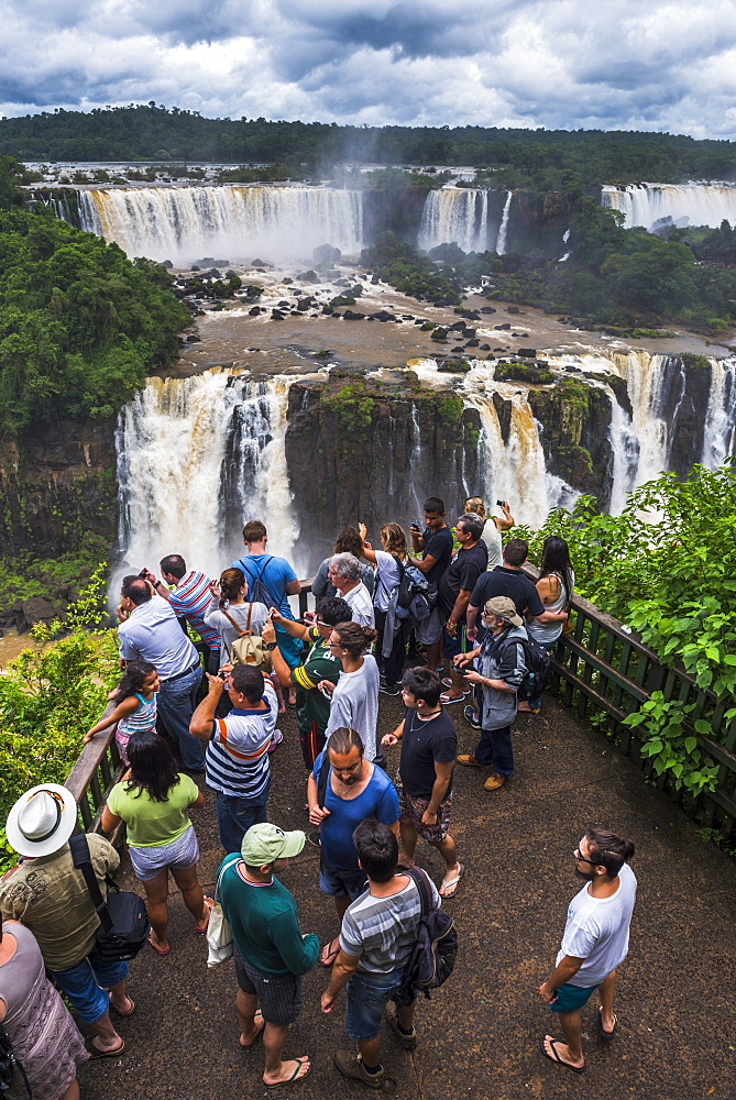 Tourists at Iguazu Falls (Cataratas del Iguacu), UNESCO World Heritage Site, on Brazilian side viewing platform, border of Brazil Argentina and Paraguay, South America