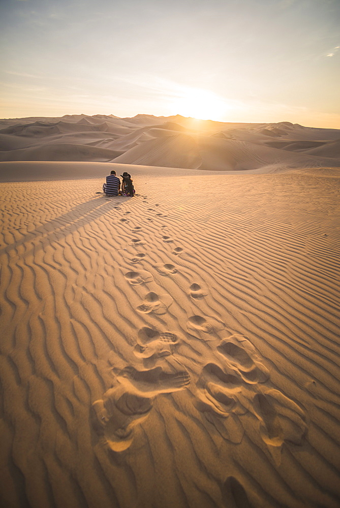 Couple watching the sunset over sand dunes in the desert at Huacachina, Ica Region, Peru, South America