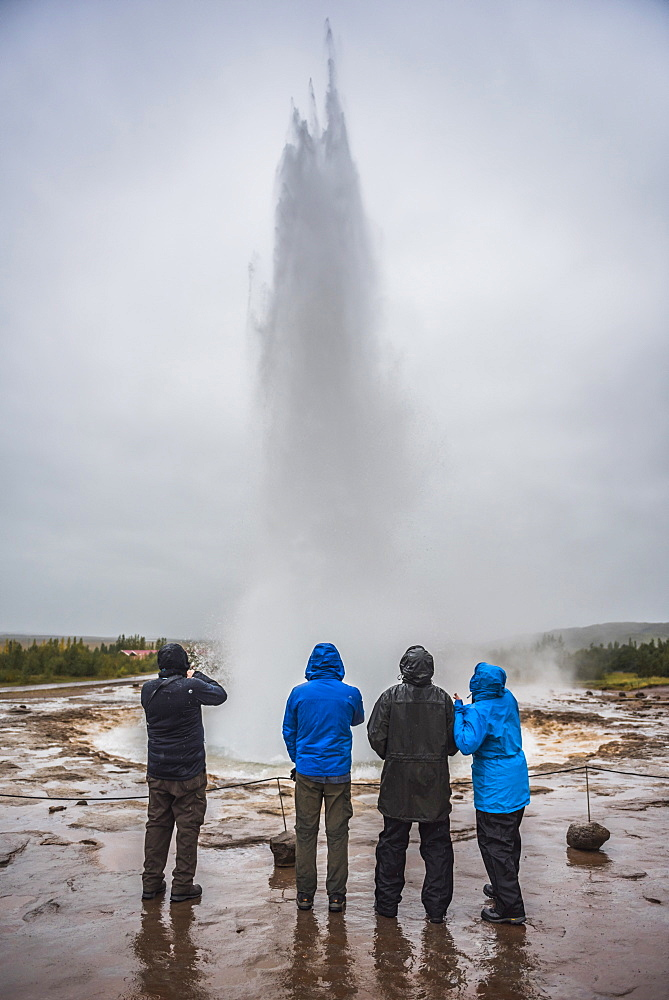 Tourists watching Strokkur Geyser erupt, Geysir, The Golden Circle, Iceland, Polar Regions