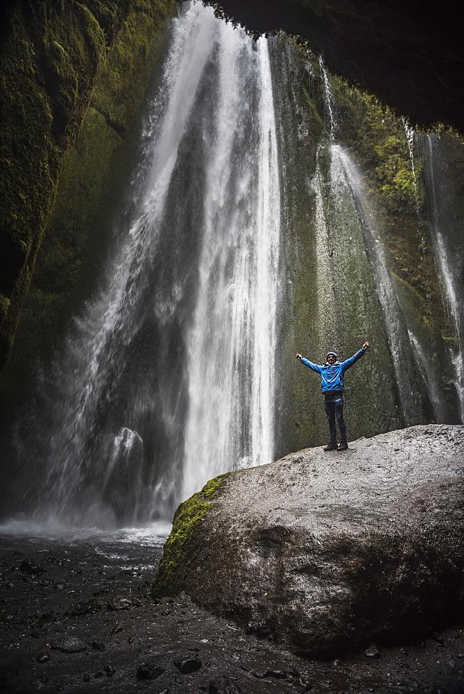 Tourist at the hidden Gljufrabui Waterfall, near Seljalandsfoss, South Iceland (Sudurland), Iceland, Polar Regions