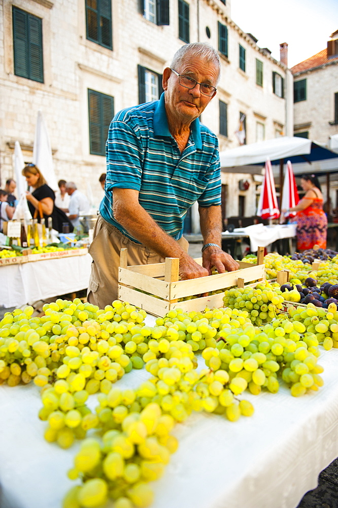 Vendor at Dubrovnik Market setting up his stall for Gundulic fruit market in Gundulic Square, Dubrovnik, Croatia, Europe