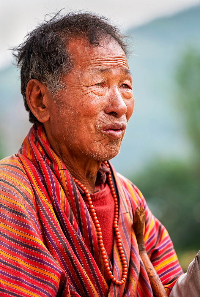 Portrait elderly Bhutanese man wearing prayer beads, Bhutan, Asia