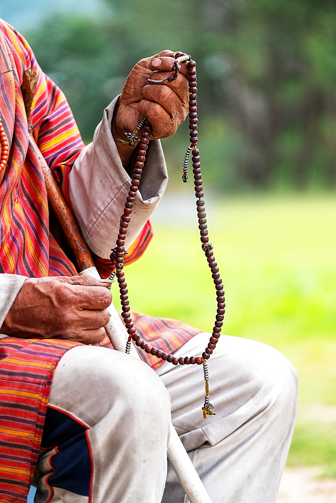 Close up of man holding Buddhist prayer beads, Bhutan, Asia