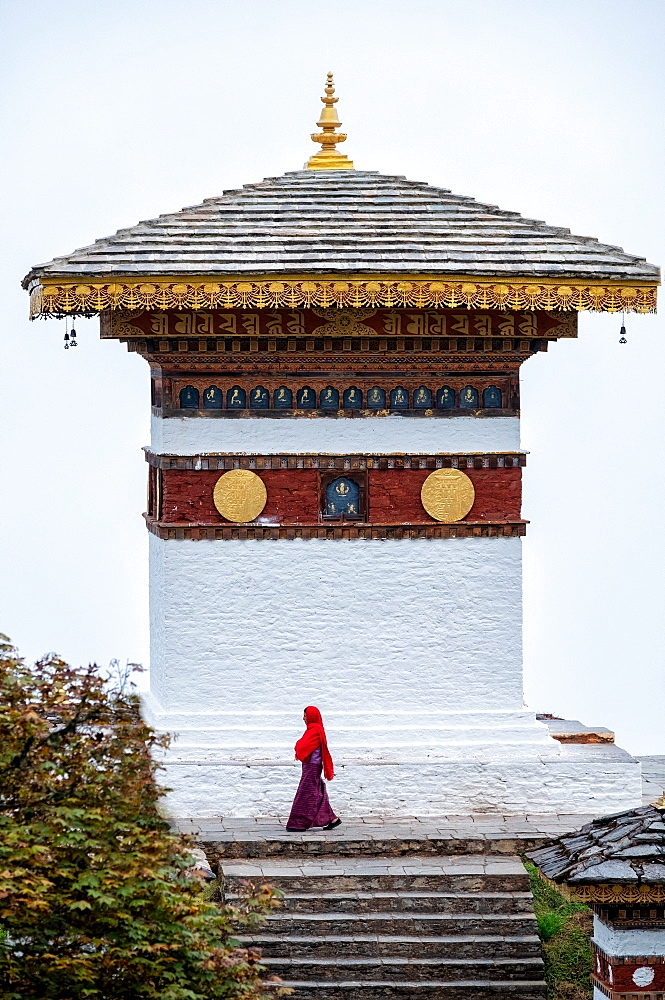 Single nun walking past temple at Dochula Pass, Bhutan, Asia