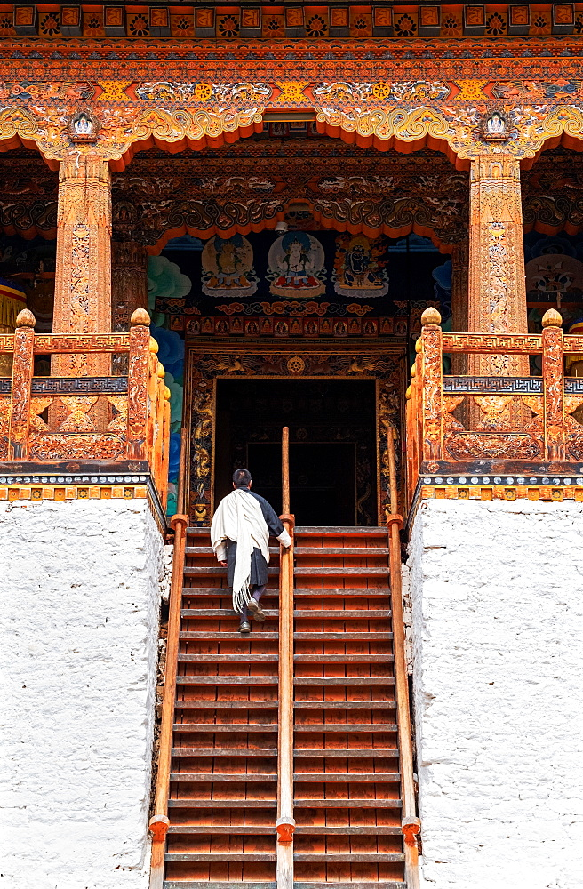 Bhutanese man in traditional dress climbing stairs into temple, Punakha Dzong, Bhutan, Asia